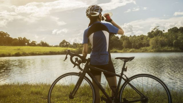 Woman cyclist relaxing drink water from the exercise
