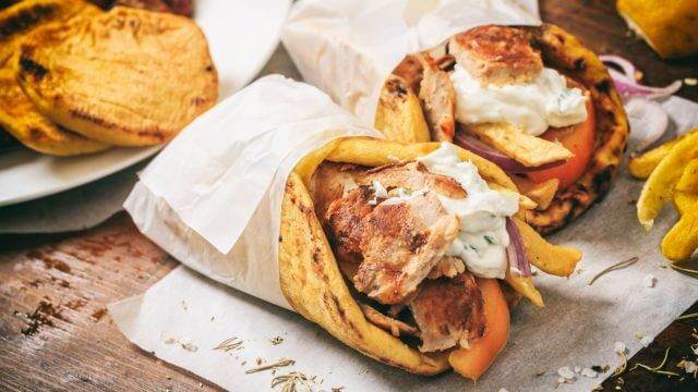 Greek gyros wraped in a pita bread on a wooden background